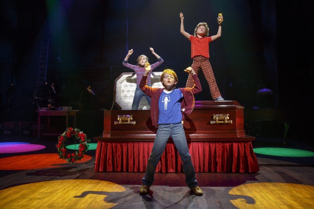 From Fun Home, kids stand on a coffin flexing their muscles