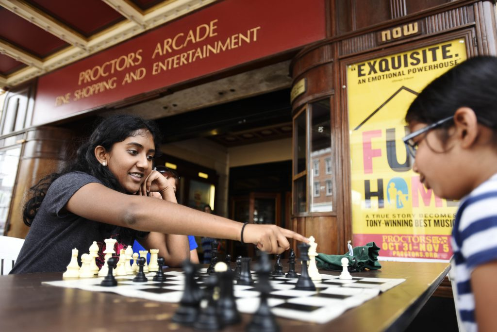 People play chess under the marquee during an event sponsored by the City Mission and Proctors Tuesday, July 11, 2017. Tables and chess boards are out every Tuesday during the summer for casual play.