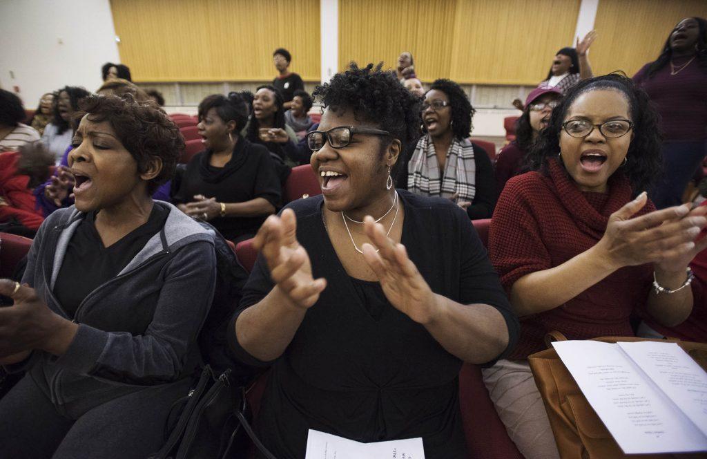 Choir members sing and clap.