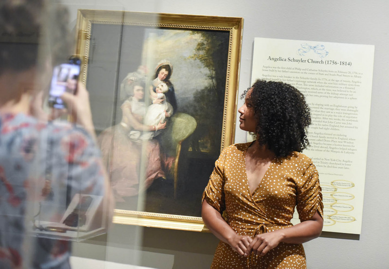 Stephanie Umoh has her picture taken with a portrait of Angelica Schuyler at the Albany Institute of History and Art in Albany Friday, August 16, 2019. Olivia Puckett plays Peggy Schuyler, Hannah Cruz plays Eliza Schuyler and Stephanie Umoh plays Angelica Schuyler in the touring production of Hamilton playing Proctors through August 25, 2019.