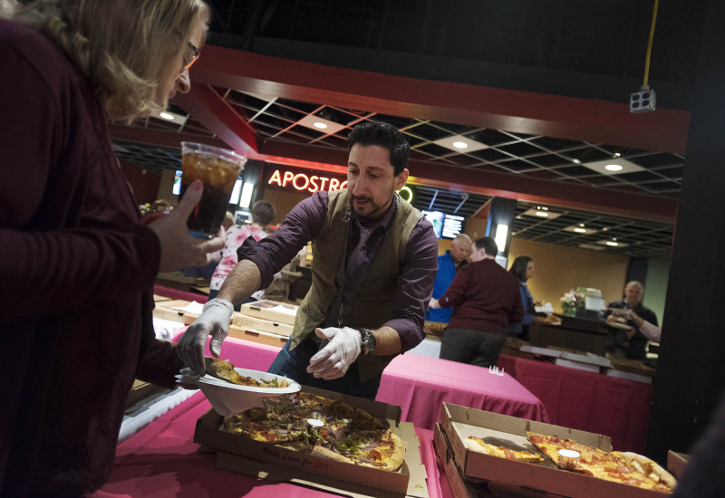 Salvatore Prizio serves pizza to a volunteer during the annual Volunteer Appreciation Night at Proctors Monday, October 29, 2018.